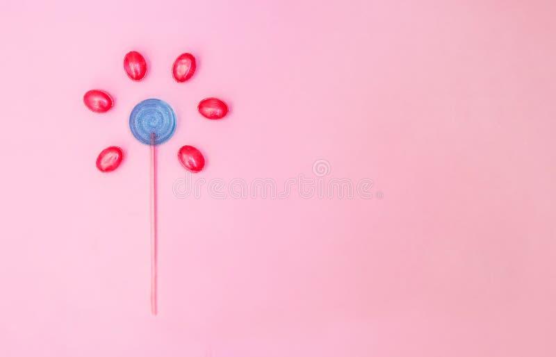 Flor hecha de la piruleta y de caramelos en fondo rosado con el espacio de la copia Concepto m?nimo imágenes de archivo libres de regalías