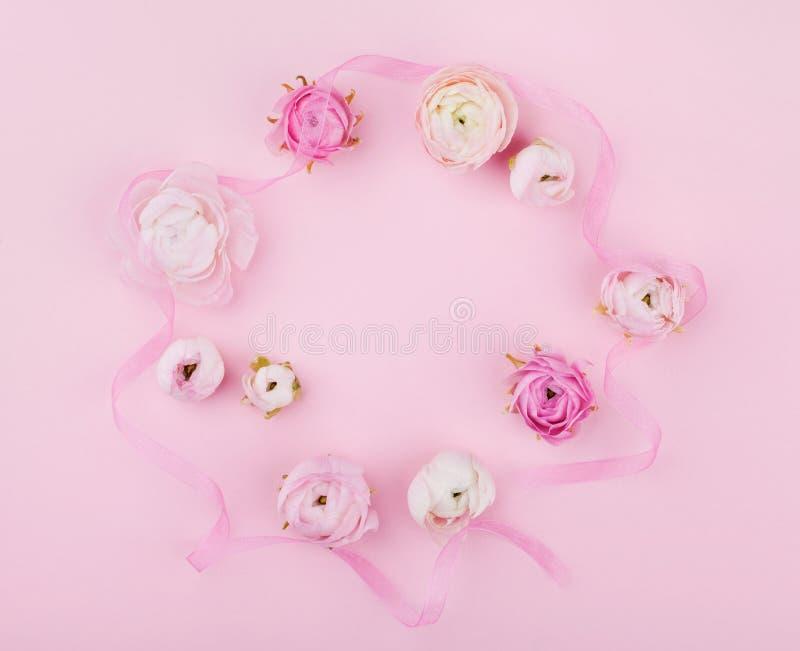 Flor hermosa de la primavera en el escritorio rosado desde arriba para casarse la maqueta o la tarjeta de felicitación el día de  fotografía de archivo