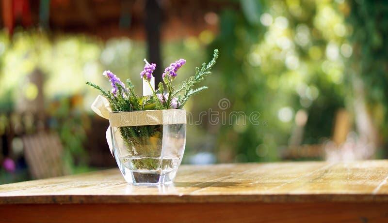Flor púrpura en florero en el backg de madera de la naturaleza de la falta de definición del espacio de la copia de la tabla fotos de archivo