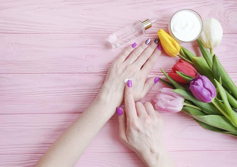 Flor poner crema cosmética del tulipán de las manos de la manicura del cuidado del tratamiento de la salud del flor femenino de l fotos de archivo libres de regalías
