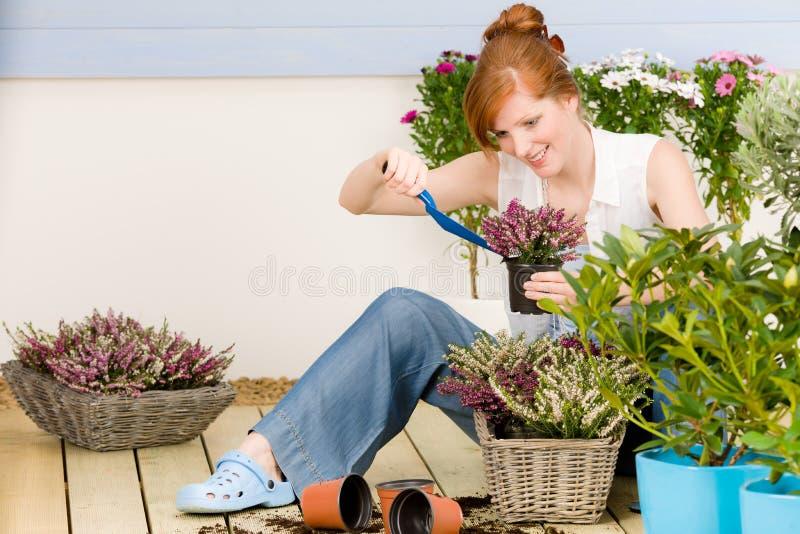 Flor potted de la mujer del redhead de la terraza del jardín del verano fotografía de archivo