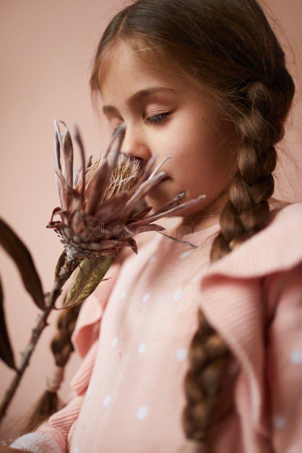 Flor que huele de la niña linda fotografía de archivo