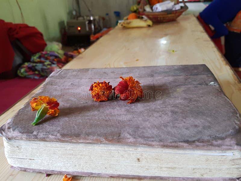 Flor sobre el libro sagrado historia del libro viejo, religioso y tradición fe Libro hindú foto de archivo libre de regalías