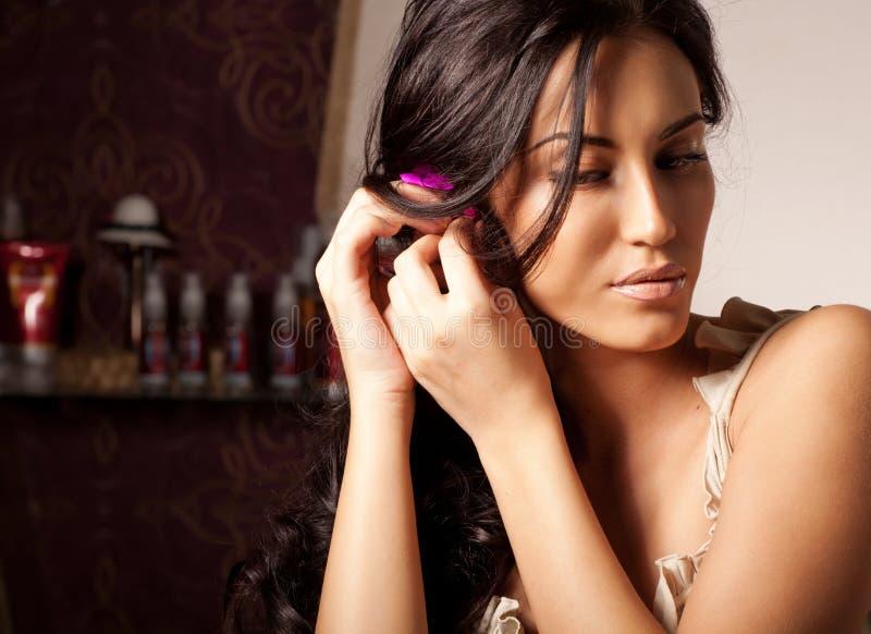 Flor triguenha nova da fixação da mulher no cabelo curly imagem de stock
