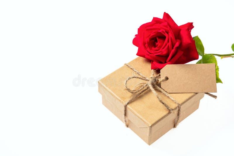 Flor vermelha de Rosa e uma caixa de presente com uma etiqueta vazia em um fundo branco, espaço para o texto foto de stock royalty free