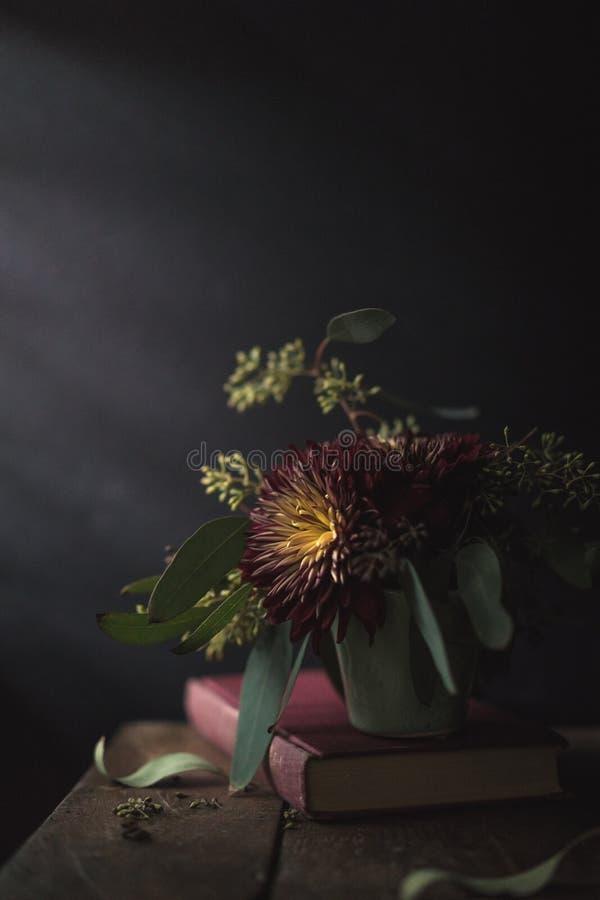 Flor vermelha e amarela do livro na vida ainda fotos de stock