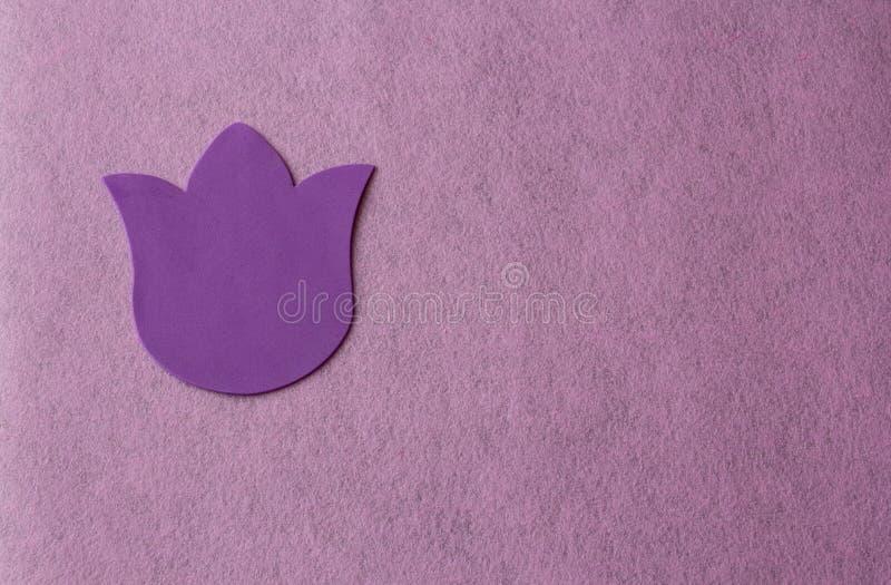 Flor violeta hecha del material suave en un fondo rosado del trapo fotos de archivo