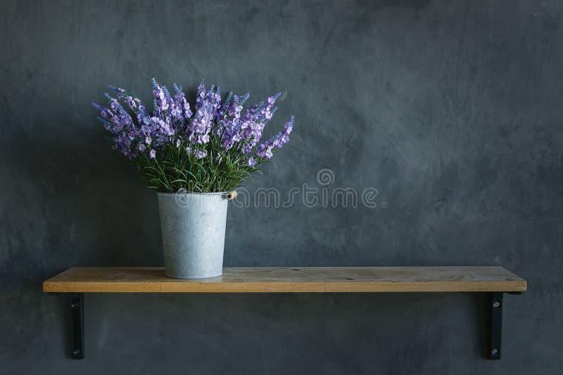 Flor violeta hermosa en el cubo del cinc ningún el piso y el cem de madera imagenes de archivo