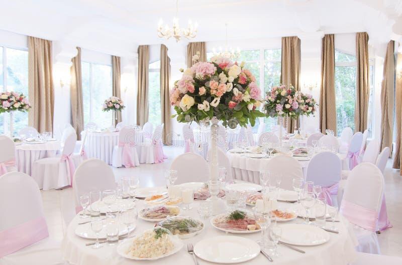 Floral ρυθμίσεις στην άσπρη στάση στυλοβατών στους πίνακες στο εστιατόριο στοκ εικόνα με δικαίωμα ελεύθερης χρήσης