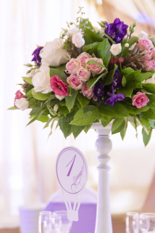 Floral στάση στυλοβατών ρυθμίσεων στους πίνακες στο εστιατόριο στοκ φωτογραφίες