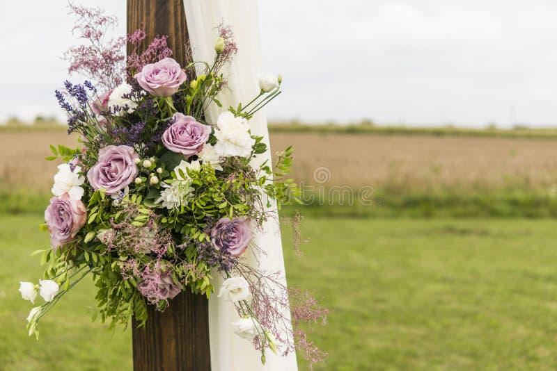Floral ξύλινη αψίδα με το άσπρο ύφασμα και φρέσκα ιώδη ρόδινα άσπρα λουλούδια με τα πράσινα φύλλα σε μια αγροτική γαμήλια τελετή στοκ εικόνες με δικαίωμα ελεύθερης χρήσης