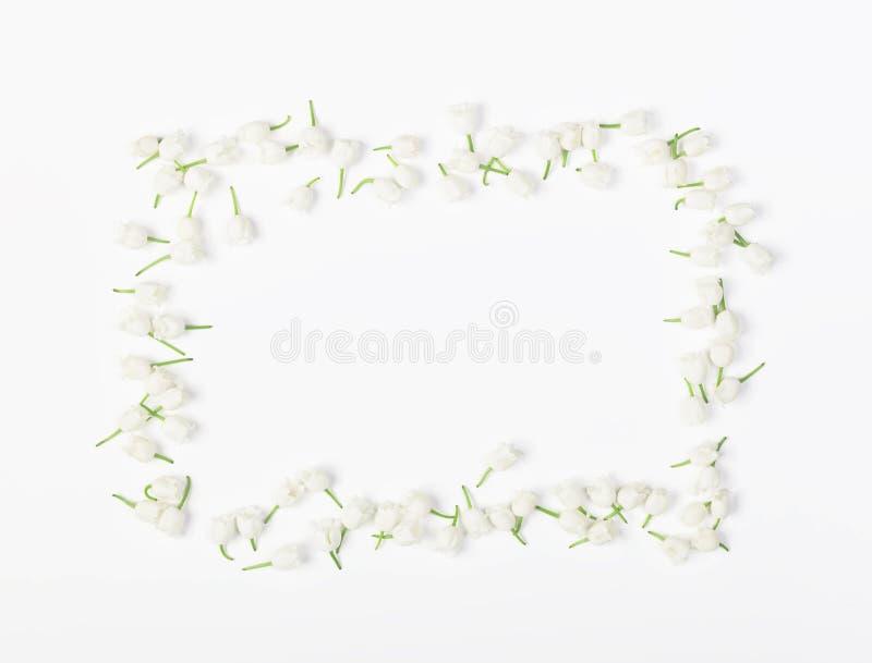 Floral πλαίσιο φιαγμένο από κρίνο της κοιλάδας που απομονώνεται στο άσπρο υπόβαθρο Επίπεδος βάλτε στοκ φωτογραφία
