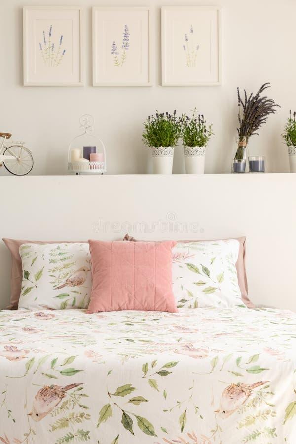 Floral ρόδινο μαξιλάρι κλινοστρωμνής και κρητιδογραφιών στο διπλό κρεβάτι στο πραγματικό pho στοκ φωτογραφία με δικαίωμα ελεύθερης χρήσης