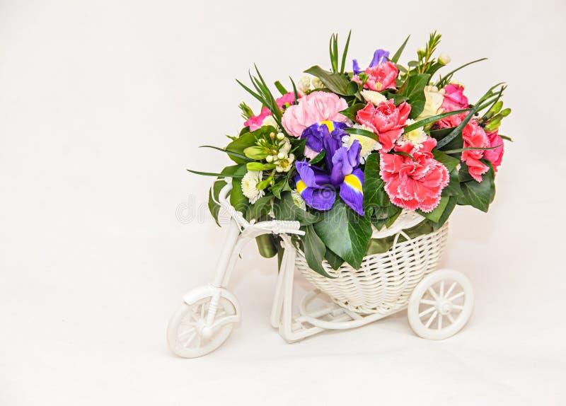 Floral ρύθμιση με το άσπρο ποδήλατο και τα χρωματισμένα τριαντάφυλλα λουλουδιών, στοκ φωτογραφία
