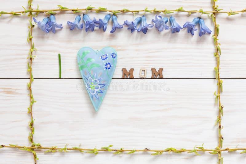 Floral σχέδιο άνοιξη με τα φρέσκα μπλε συγχαρητήρια ημέρας λουλουδιών και μητέρων υάκινθων στο άσπρο ξύλινο υπόβαθρο στοκ φωτογραφίες
