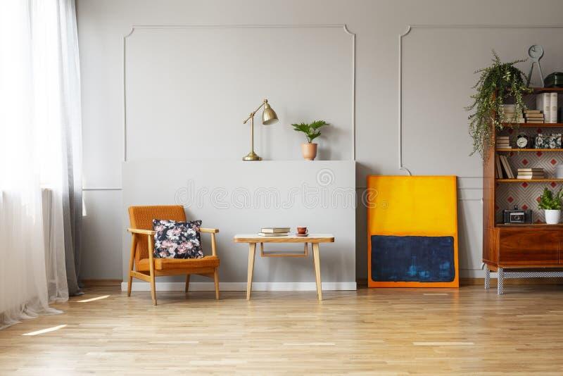 Floral τυπωμένη ύλη σε μια πορτοκαλιά επικαλυμμένη πολυθρόνα σε ένα κομψό εσωτερικό καθιστικών με το πάτωμα σκληρού ξύλου και θέσ στοκ εικόνα