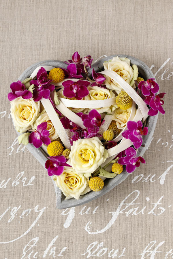 Floral arrangement with roses and orchids in heart shape. Party decoration royalty free stock photography