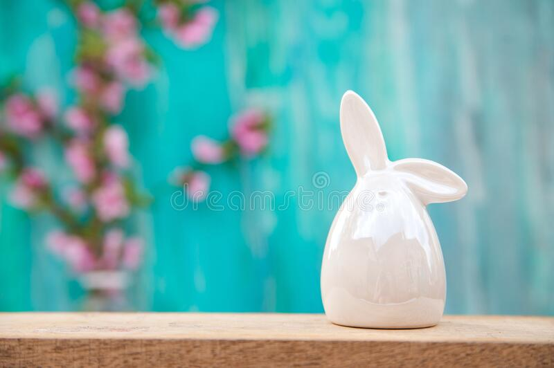Floral background for text and a white porcelain bunny. Wooden table top with flowers close-up and copy space. Easter rabbit on a royalty free stock images