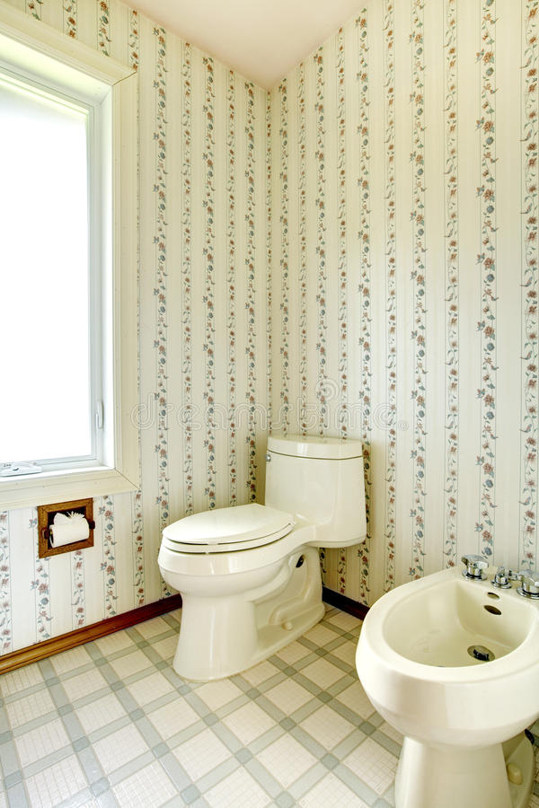 Floral bathroom with toilet and bidet. Refreshing white bathroom with window. View of white toilet and bidet stock photography