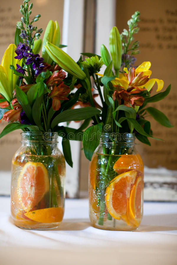 Floral bouquets in jars with oranges royalty free stock photography
