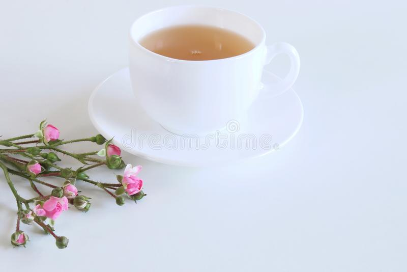 Floral composition made of beautiful pink roses on white wooden background with a cup of tea. Feminine office desk, styled stock i royalty free stock photography