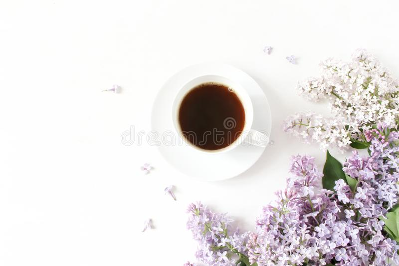Floral composition made of beautiful purple lilac, syringa flowers on white wooden background with cup of coffee. Feminine office desk, styled stock image stock photo