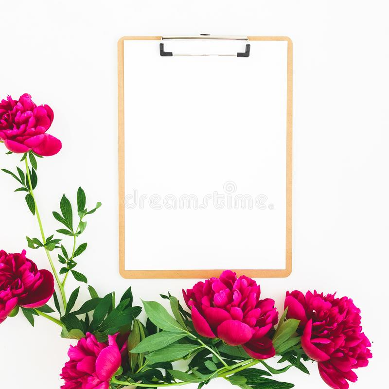 Floral composition made of red peony flowers and clipboard with paper on white background. Flat lay, top view stock photography