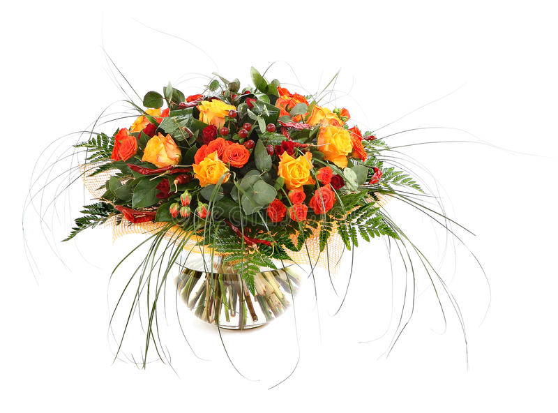 Floral composition of orange roses, hypericum and fern. Flower arrangement in a transparent glass vase. Isolated on white. Flower arrangement of orange roses royalty free stock photography