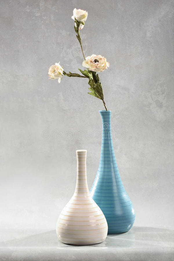 Floral decoration. A stylish arrangement of white flowers on a single stem in an elegant blue vase royalty free stock photo