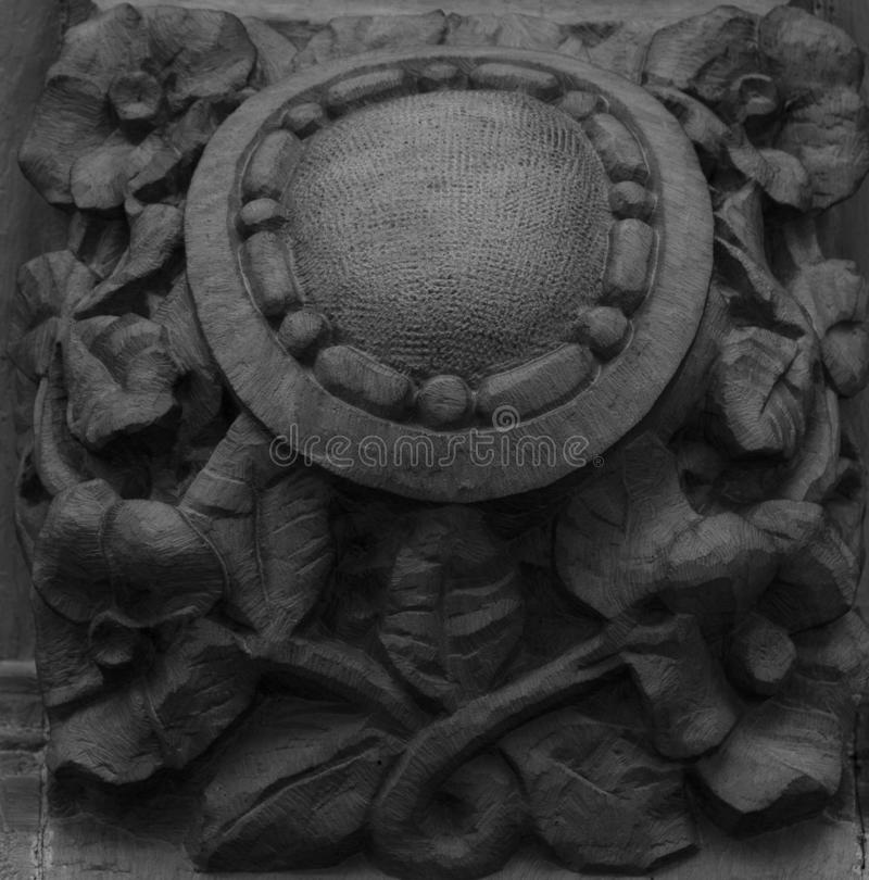 Floral decoration surrounding the empty shield. Shot in black and white detail on the facade of this historic building representing some character, animal or royalty free stock photography