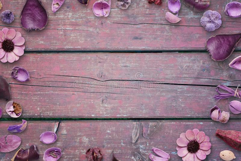 Floral decorations on pink, purple wooden desk with free space in the middle for text, photo or product presentation.  stock image