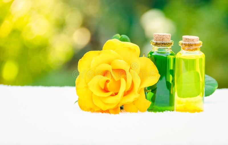 Floral essential oils and fragrant rose. Rose oil and a white towel. Spa concept. Aromatherapy and massage. royalty free stock images