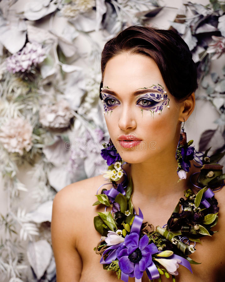 Floral face art with anemone in jewelry, sensual young brunette woman royalty free stock image