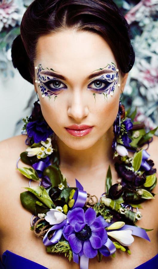 Floral face art met anemone in juwelen, sensuele jonge brunette vrouw in studio close stock fotografie