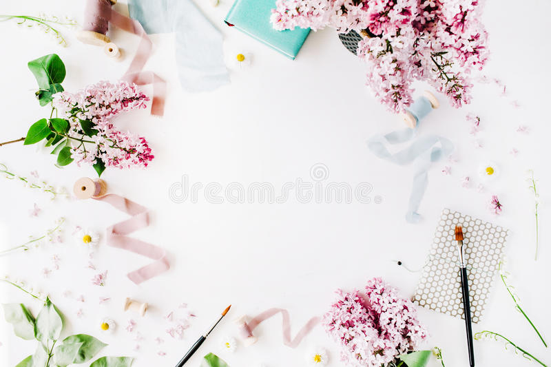 Floral frame with lilac flower, chamomile, fresh branches and spool with blue and beige ribbon, notebook isolated on white royalty free stock photography