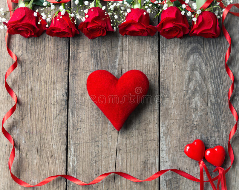 Floral frame with red roses on wooden background stock image