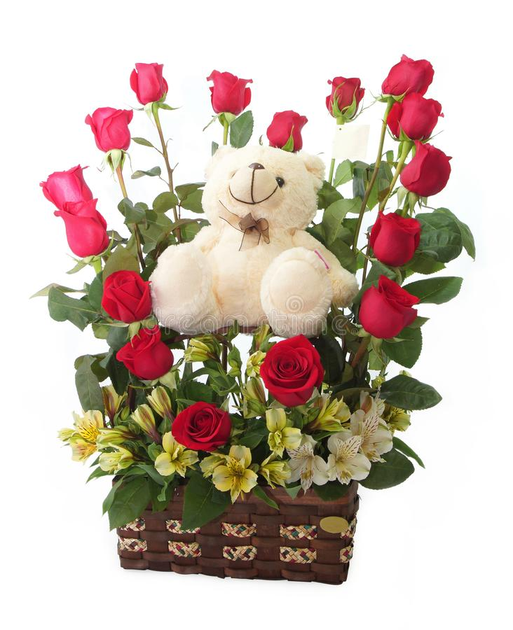 Floral gift arrangement made with red roses with long stems inside a brown pot with teddy bear royalty free stock images