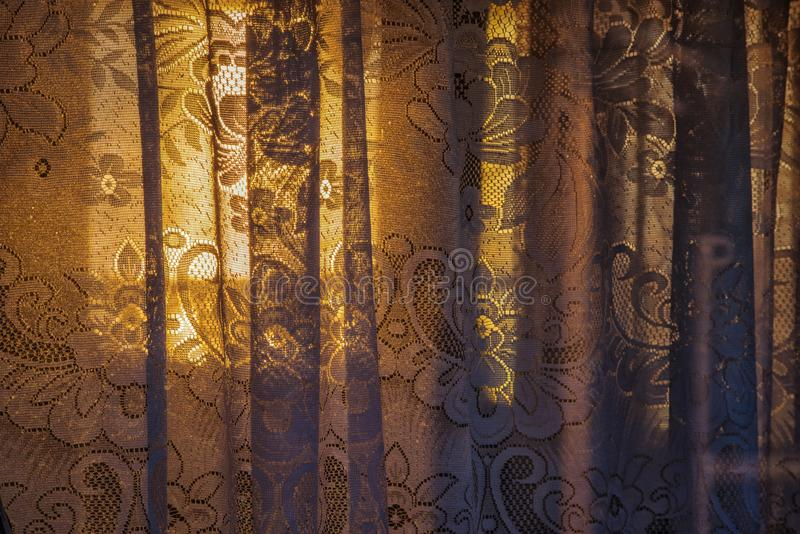 Floral lace curtains background texture. Old floral lace curtains on the window of a boat with sunset light through them royalty free stock photo