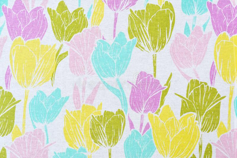 Floral pattern from multi-colored tulips on a white cotton table royalty free stock photos