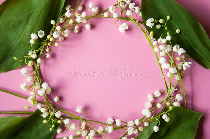 Floral pink background with fresh flowers. Lilies of the valley frame. Spring greeting card. Congratulations on Mother`s Day, Birt royalty free stock images