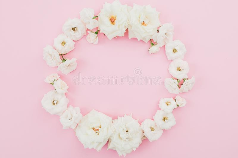 Floral round frame made of white roses on pink background. Flat lay, top view. Pastel background. royalty free stock images