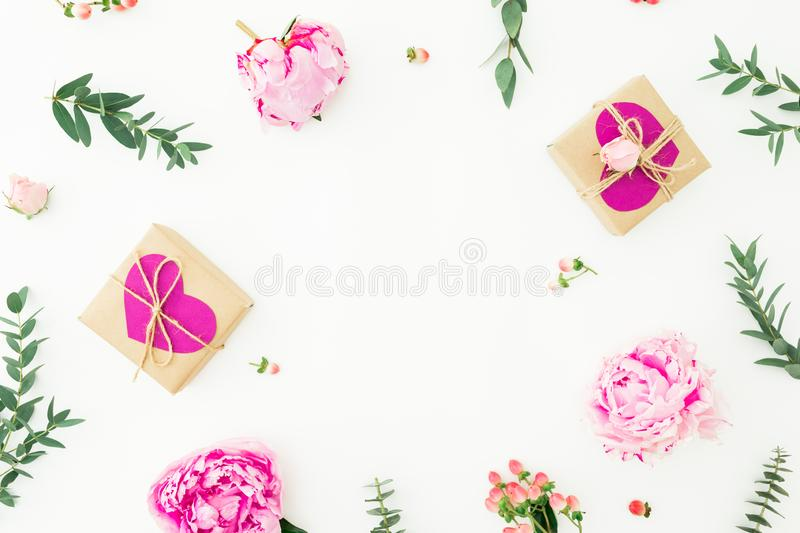 Floral round frame of pink peonies, roses, hypericum and eucalyptus branches and gifts on white background. Love composition stock photos