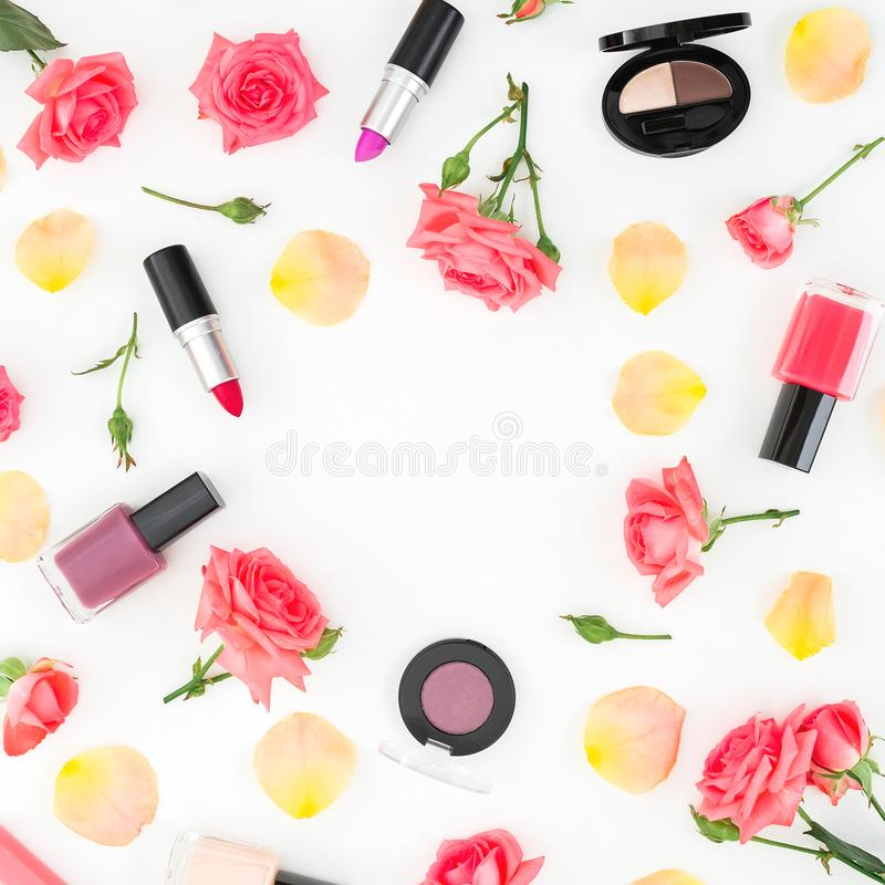 Floral round frame with roses flowers and feminine cosmetics on white background. Flat lay, top view royalty free stock image