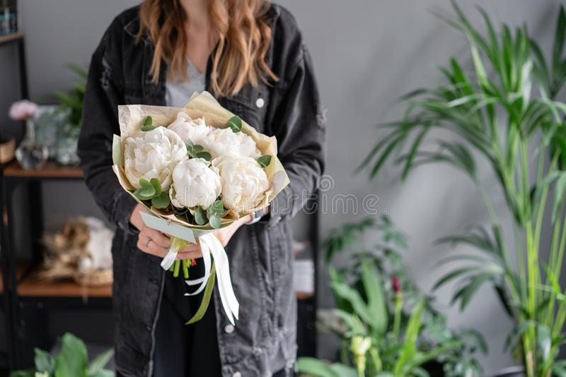 Floral shop and flowers delivery concept. White peonies in womans hands. Beautiful fresh peony flower for catalog or royalty free stock photo