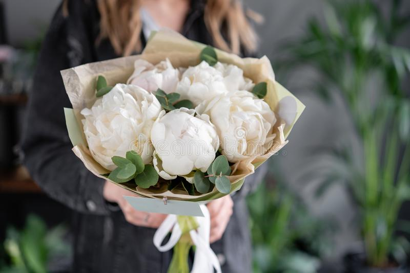 Floral shop and flowers delivery concept. White peonies in womans hands. Beautiful fresh peony flower for catalog or stock photography