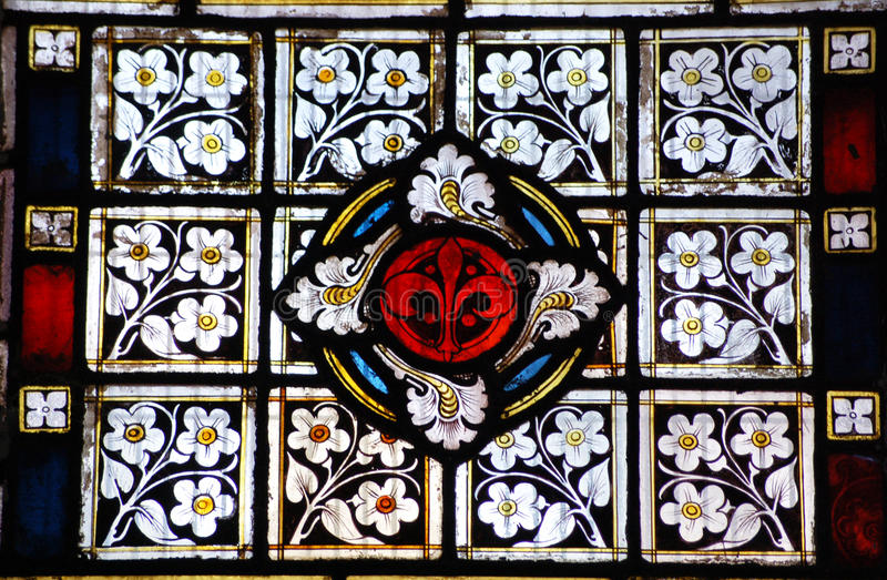 Floral stained glass. A Victorian panel of stained glass. With a fleur de lys surrounded by forget me nots stock image