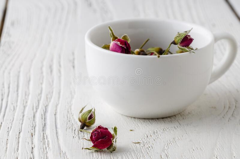 Floral tea with rose hips in bowl royalty free stock image