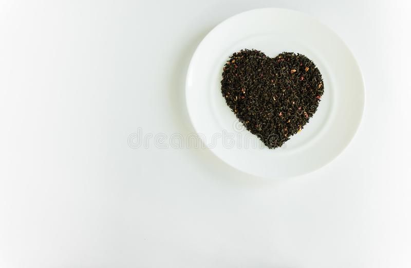 Floral tea in the shape of a heart on a white plate. Floral fragrant heart-shaped tea on a white plate for food background white royalty free stock photography