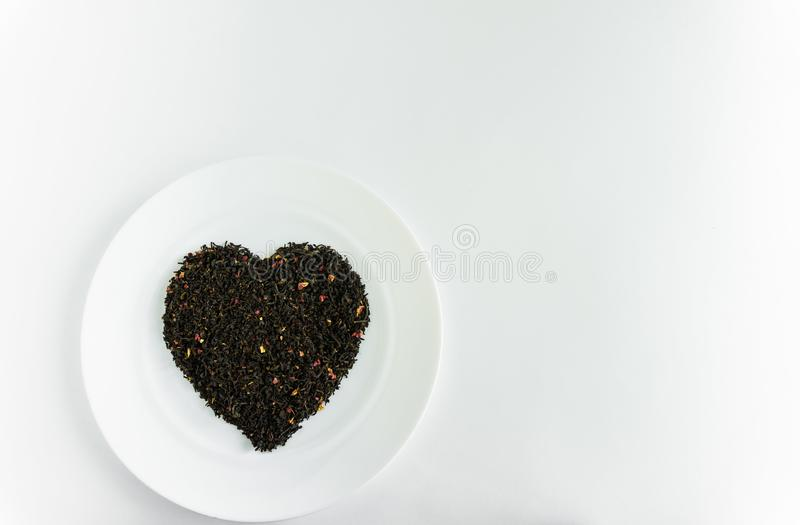 Floral tea in the shape of a heart on a white plate. Floral fragrant heart-shaped tea on a white plate for food background white royalty free stock photo