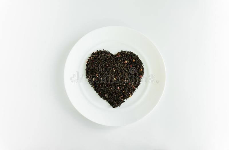 Floral tea in the shape of a heart on a white plate. Floral fragrant heart-shaped tea on a white plate for food background white royalty free stock images